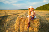 Little girl in a field with hay rolls at sunset - 160396489