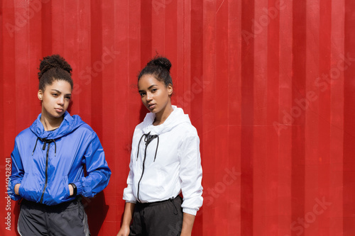 Two young female in sportswear posing together at wall Poster