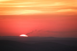 Large sun setting over the horizon in the hills covered with mist with smoking chimneys