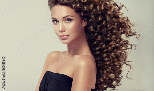 Brunette girl with long and shiny curly hair . Beautiful model with wavy hairstyle .  © Sofia Zhuravetc