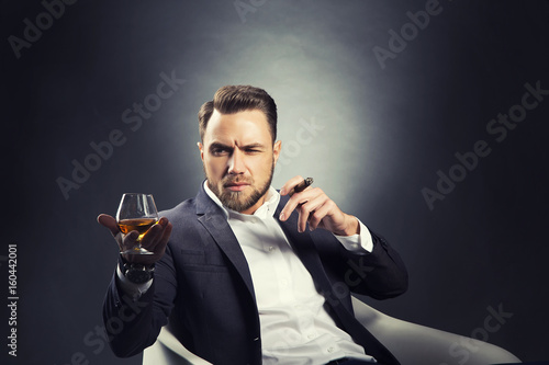 Portrait of handsome man drink cognac with cigar over dark studio background