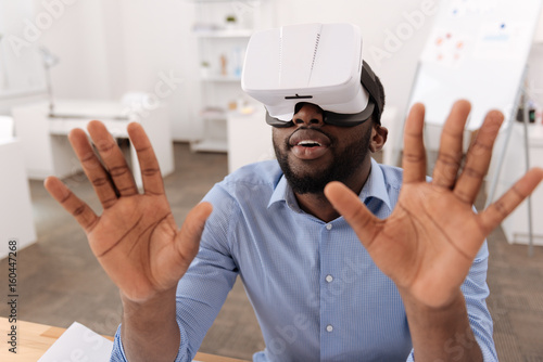Serious nice man pressing his hands to the virtual screen