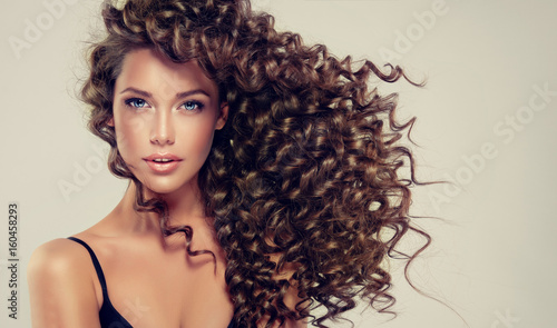 Leinwanddruck Bild Brunette girl with long and shiny curly hair . Beautiful model with wavy hairstyle .