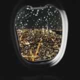 New York City Manhattan at night through a plane window in the rain