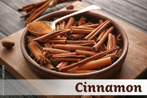 Bowl with cinnamon sticks and spoon of powder on wooden background