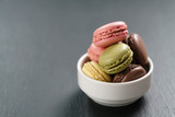 assorted macarons in white bowl on slate background