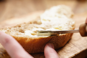 young female hands spreading butter on bread