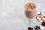 Chocolate smoothie with banana and nuts on a grey stone table.