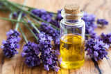 A bottle of essential oil with fresh lavender twigs - 160554813