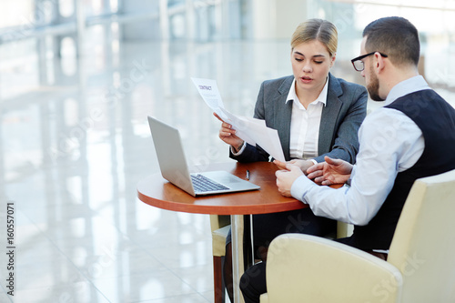 Portrait of young businesswoman consulting client on contract terms finalizing the deal