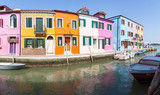 Burano, Venice, Veneto, Italy, Row of colorful fisherman houses on a canal with reflections in a panorama view. Burano island is famous for its lace and brightly colored buildings