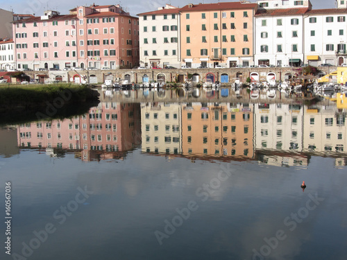 Picturesque ancient residential neighborhood near the city center of Livorno . Tuscany, Italy . Houses and boats are reflected in the tranquil water