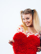 Happy woman holding heart shaped pillow