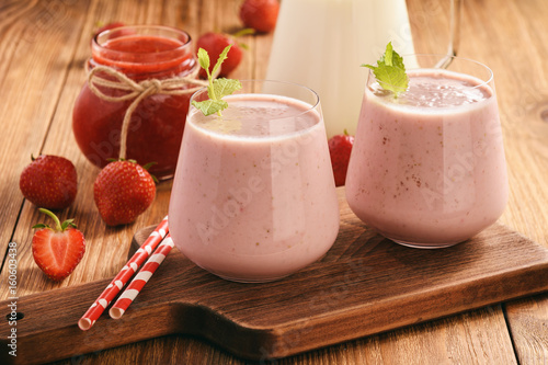 Foto op Aluminium Milkshake Healthy beverage- strawberry milkshake in glasses on wooden background.