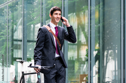Young confident man wearing business suit while talking on mobile phone after bike commuting