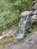 Rushing waterfall flowing over granite boulders in Sofiyivsky Park, Uman City, Ukraine, during the Indian summer