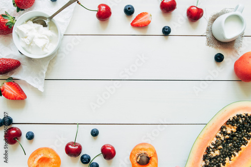 Summer fruits. Fresh juicy berries and papaya on the white wooden table, top view
