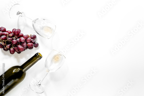 Composition with bottle of red wine, wineglasses and red grape on white background copyspace top view - 160637066