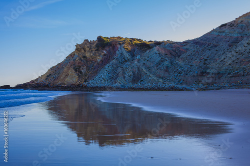 Plagát Beautiful sandy beach on the coast of Portugal at sunset, the rock is reflected