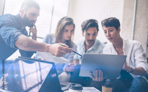 Teamwork process.Young coworkers work with new startup project in office.Woman holding touch pad in hands,bearded man pointing to screen.Horizontal, blurred, flare.