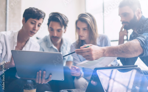 Young partners making research for new business direction.Young businessman working modern laptop and showing documents to young colleague.Business people meeting concept.Blurred background.