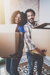 Smiling young black african couple moving boxes into new home together and making a successful life.Cheerful family standing in empty new apartment.Vertical.Blurred background.Cropped.Flares.