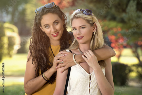 two girls blonde and brunette hugs in a park on a beautiful spring day Poster