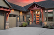 Beautiful Luxury Home Exterior at Sunset: Front Entrance with Elegant Front Door and Partial View of Garage and Driveway. Colorful Sunset Backdrop
