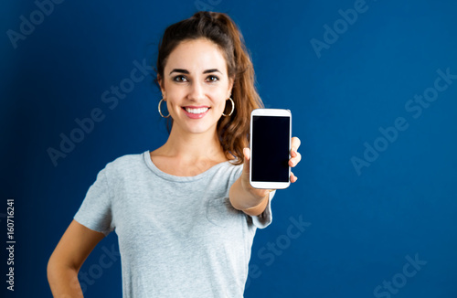 Happy young woman showing smartphone monitor