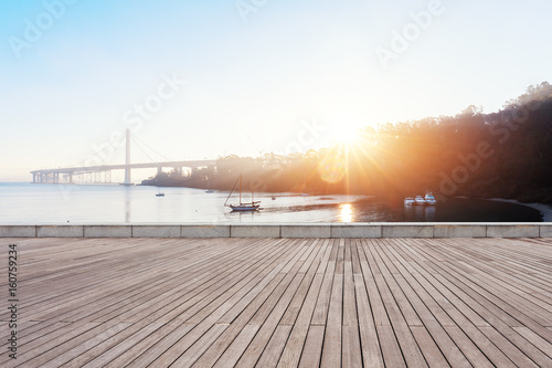 empty wooden floor near modern suspension bridge with sunbeam Poster
