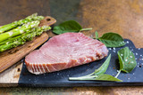 Fresh tuna steak with herbs and green asparagus.