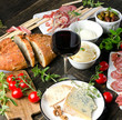 Different meat and cheese products with wine on a  dark wooden table