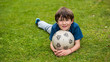 Young boy laying on the grass holding a soccer ball
