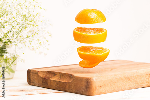 Sliced whole orange flying above a wooden chopping board