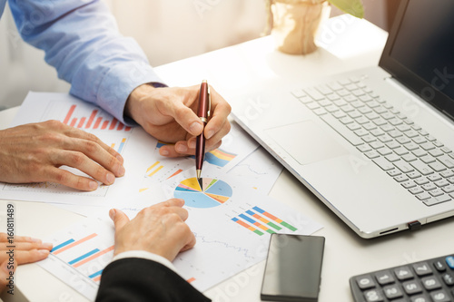 Fridge magnet people at office analyzing business financial graph reports