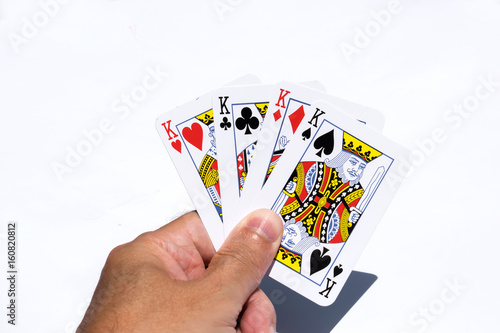 Poker cards on white backgrounds.Four kings in hand плакат