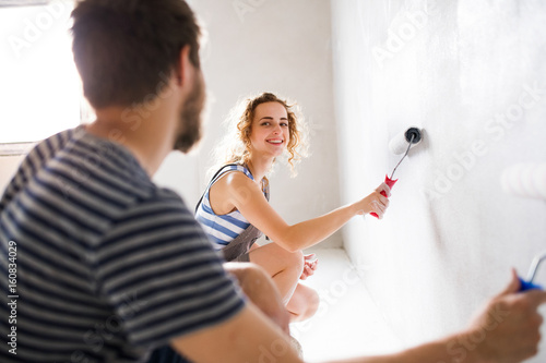 Young couple painting walls in their new house. - 160834029