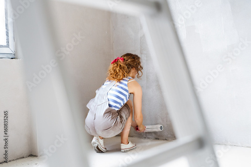 Young woman painting walls of her new house. - 160835265