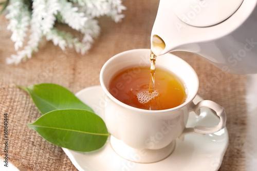Close up pouring hot black tea in a white tea cup ,  Tea ceremony time concept © Cozine