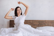 Excited woman waking up with arms outstretched