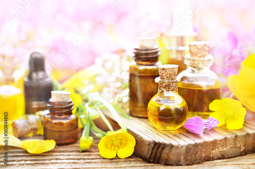 Essential oil bottles on medicinal flowers and herbs background Poster
