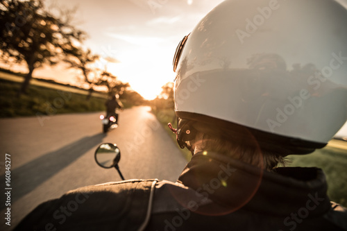 Man riding sportster motorcycle during sunset.