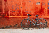 old bike standing at colorful red wall