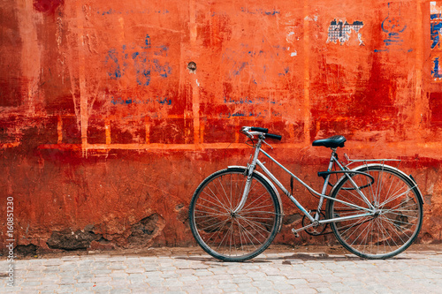 Staande foto Fiets old bike standing at colorful red wall