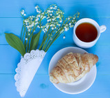 Bouquet of lilies of the valley, cup of tea and a croissant on the blue wooden background.
