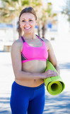 Smiling sportswoman with gymnastic mat