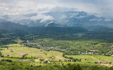 Panorama view of green land with sunlight and mountain covered by cloud and fog in countryside of Thailand on rainy season.