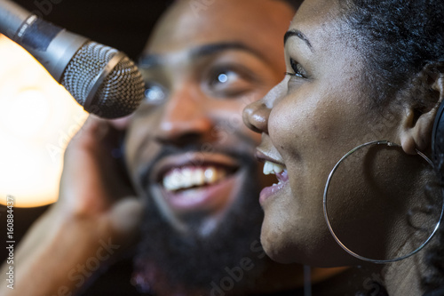 Black male and female singing in a recording studio Poster