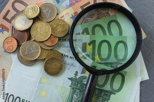 Magnifying glass on pile of Euro banknotes and coins as business financial tax concept