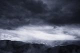 dramatic storm clouds in dark landscape
